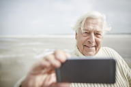 Smiling senior man taking selfie with cell phone on beach - CAIF05183