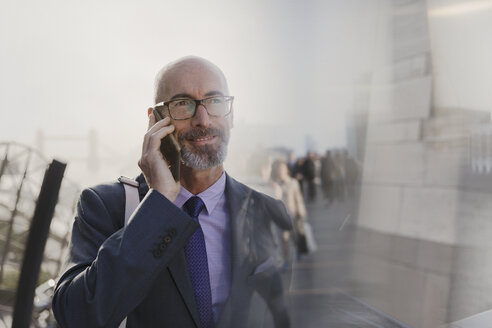 Businessman talking on cell phone on urban street - CAIF05186