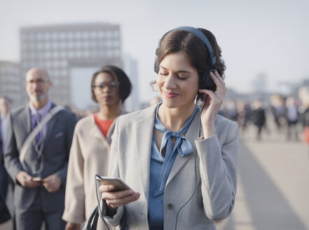 Businesswoman smiling, listening to music with headphones and smart phone on urban pedestrian bridge - CAIF05204