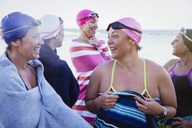 Female open water swimmers talking and drying off with towels on beach - CAIF05222