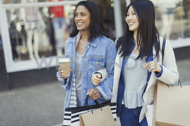 Smiling women friends walking arm in arm along storefront with coffee and shopping bags - CAIF05255