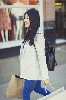 Smiling young woman walking along storefront with shopping bags - CAIF05288