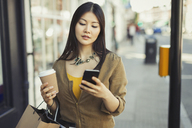 Young woman with coffee texting with cell phone on urban sidewalk - CAIF05291