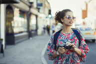 Young female tourist in sunglasses with camera on urban street - CAIF05297