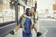 Playful young couple piggybacking on urban street - CAIF05303