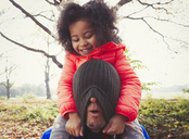 Playful daughter pulling stocking cap over fathers face in autumn park - CAIF05309