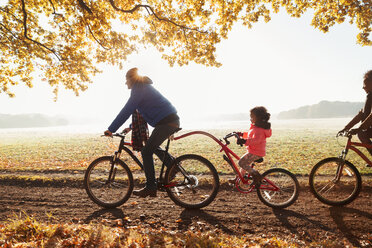 Father and daughter bike riding with trailer bike in sunny autumn park - CAIF05315