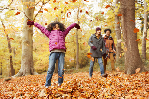 Playful girl throwing autumn leaves in woods - CAIF05321