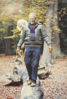 Senior couple walking on log in autumn woods - CAIF05324