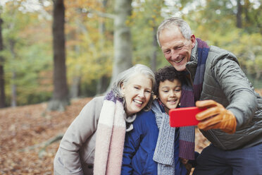 Grandparents and grandson taking selfie in autumn woods - CAIF05327