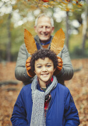 Grandfather holding autumn leaves behind grandson in woods - CAIF05330