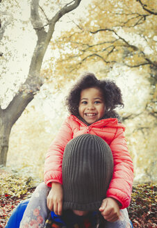 Portrait smiling daughter pulling stocking cap over fathers head in autumn park - CAIF05336