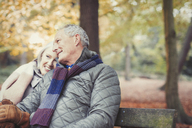 Affectionate senior couple on bench in autumn park - CAIF05342