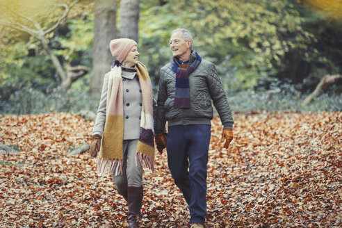 Senior couple walking in autumn leaves in park - CAIF05345