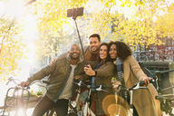 Smiling friends with bicycle taking selfie with selfie stick on urban bridge - CAIF05357