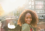 Portrait smiling young woman along urban canal, Amsterdam - CAIF05360