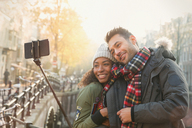 Affectionate couple hugging and taking selfie with selfie stick on autumn bridge, Amsterdam - CAIF05381