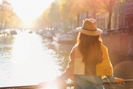 Woman looking at sunny autumn canal view, Amsterdam - CAIF05384