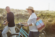 Mature couple walking bicycles on sunny beach grass path - CAIF05393