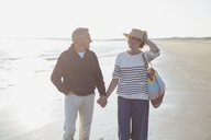 Smiling mature couple holding hands and walking on sunny beach - CAIF05396