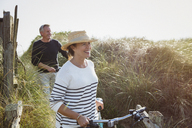 Mature couple walking bicycles along sunny beach grass - CAIF05399