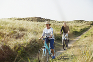 Mature couple riding bicycles on sunny beach grass path - CAIF05417