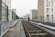 France, Paris, man walking along abandoned railway tracks - AFVF00282