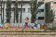 Woman jumping in the air between abandoned railway tracks - AFV00285