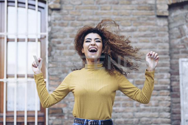 Portrait of happy young woman tossing her hair - JSMF00072