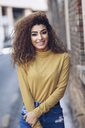 Portrait of smiling young woman with curly hair - JSMF00075