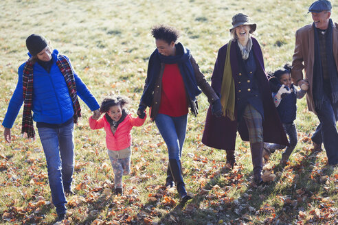 Multi-generation family holding hands and walking in sunny autumn park - CAIF05432