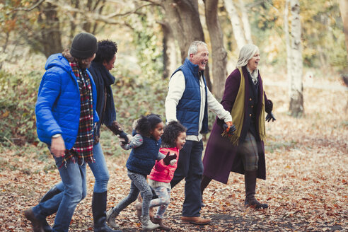 Multi-generation family holding hands walking in autumn park - CAIF05435