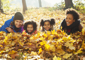 Portrait smiling young family laying in autumn leaves in sunny woods - CAIF05438