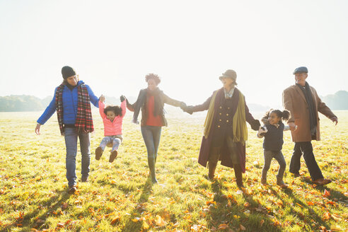 Playful multi-generation family walking in sunny autumn park grass - CAIF05444