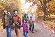 Multi-generation family walking on path in autumn park - CAIF05450