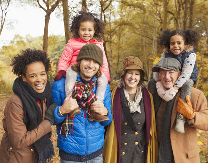 Portrait smiling multi-generation family in autumn woods - CAIF05453