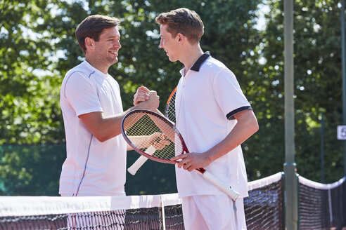 Smiling young male tennis players handshaking in sportsmanship over net on tennis court - CAIF05477