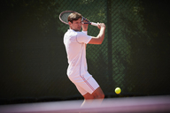 Young male tennis player playing tennis, swinging at tennis ball on sunny tennis court - CAIF05480