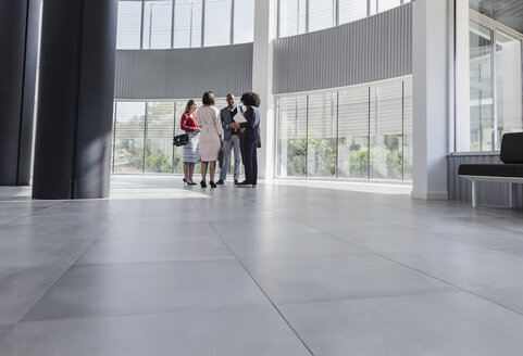 Business people talking in modern office lobby - CAIF05504