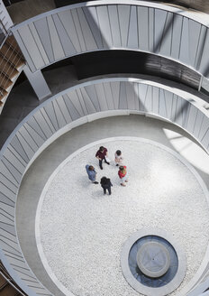 View from above business people talking in round, modern office atrium courtyard - CAIF05516