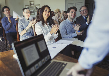 Smiling business people clapping for businessman leading conference presentation at laptop - CAIF05564