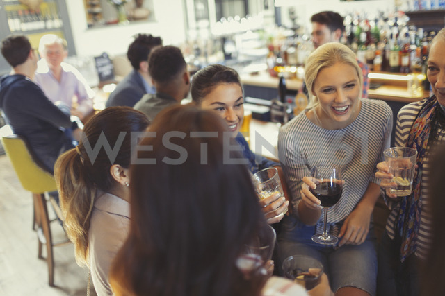 Women friends drinking and talking at bar - CAIF05573