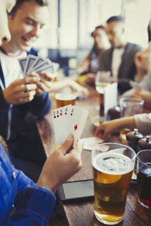 Woman holding aces four of a kind playing poker and drinking beer with friends at bar - CAIF05576