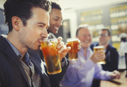 Man drinking beer with friends at bar - CAIF05582