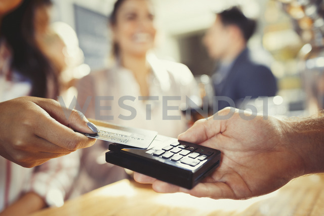 Woman with credit card paying bartender with contactless payment at bar - CAIF05600