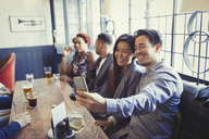 Smiling couple taking selfie with camera phone at table in bar - CAIF05606
