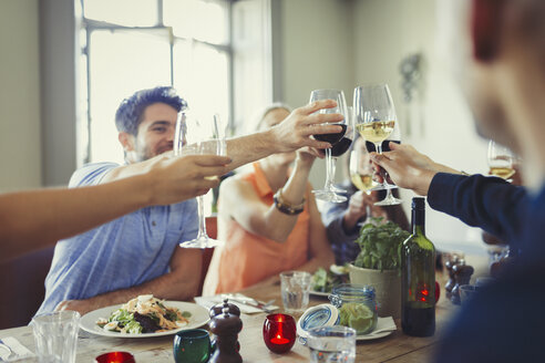 Friends celebrating, toasting wine glasses and dining at restaurant table - CAIF05618