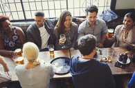 Overhead view of friends drinking beer and wine at table in bar - CAIF05624