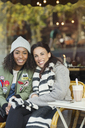 Portrait smiling young women friends in warm clothing at sidewalk cafe - CAIF05648