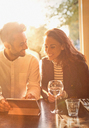 Young couple drinking white wine and using digital tablet in cafe - CAIF05654